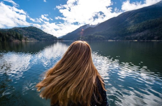 Person with long hair looking over lake